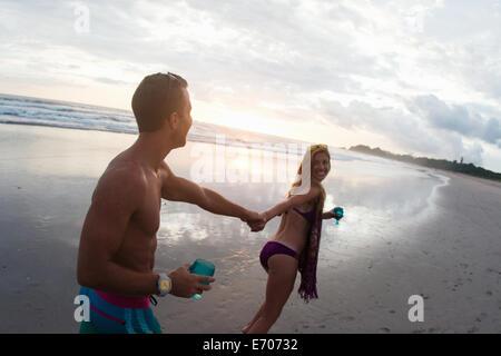 Mid adult woman leading boyfriend by hand on beach, Nosara, Guanacaste, Costa Rica - Stock Photo