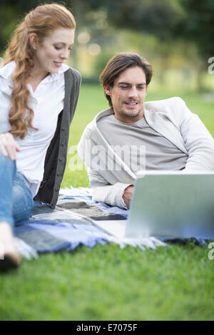 Businessman and female colleague looking at laptop in park - Stock Photo