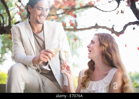 Couple toasting each other with champagne in garden restaurant - Stock Photo