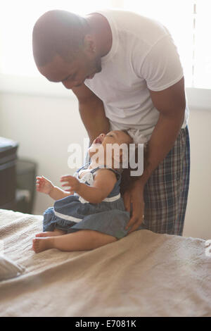 Father laughing with baby daughter - Stock Photo