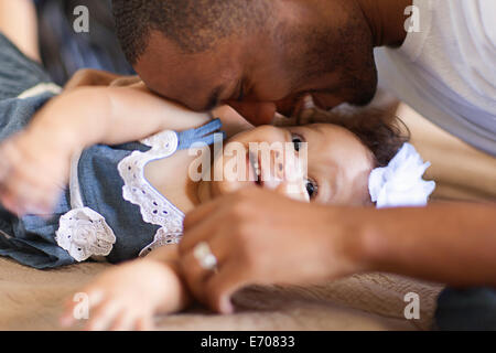 Father playing with baby daughter - Stock Photo