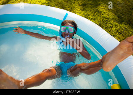 High angle view of girl in snorkel mask in garden paddling pool - Stock Photo