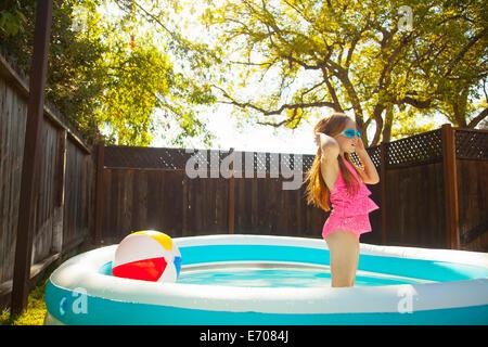 Girl in swimming goggles in garden paddling pool - Stock Photo