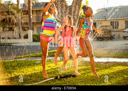 Three girls running and jumping in garden sprinkler - Stock Photo
