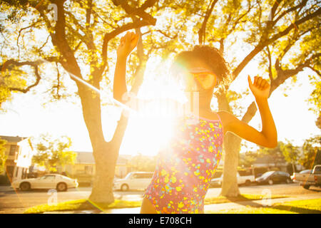 Girl in dancing in scuba goggles in garden - Stock Photo