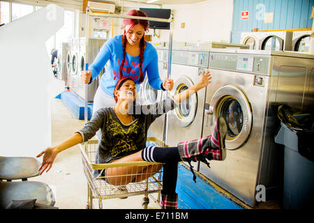 Two young women in laundromat, one pushing the other along in trolley - Stock Photo