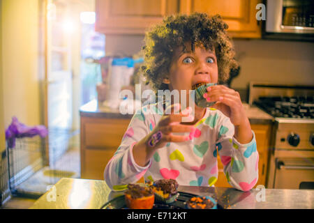 Portrait of surprised girl eating cupcakes at kitchen counter - Stock Photo