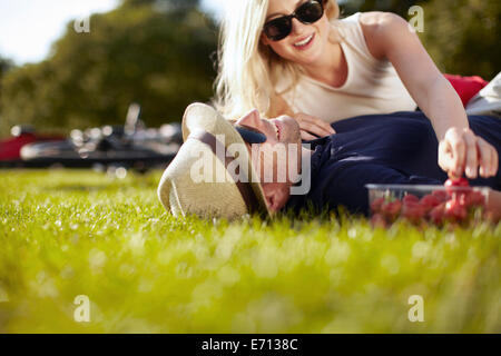 Young woman reaching for strawberries whilst boyfriend lying in park - Stock Photo