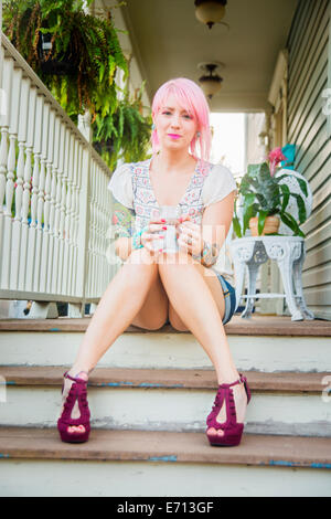Portrait of young woman with pink hair sitting on porch steps - Stock Photo