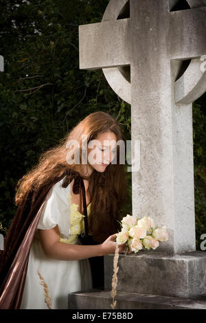 Young victorian widow putting flowers on a grave - Stock Photo