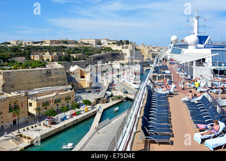 Sun deck of a large tall modern cruise liner with views over Valletta city & passengers  sunbathing rather than - Stock Photo