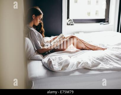 Side view of young woman sitting on her bed reading a book at home in bedroom - Stock Photo