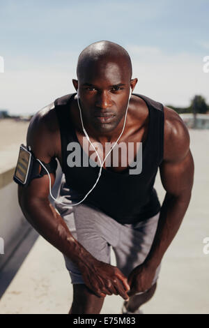 Fit young guy on his mark to start a run. Focused young male athlete outdoors looking at camera. Muscular African - Stockfoto