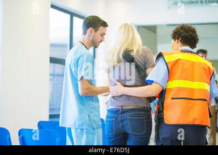 Paramedic and nurse helping patient in hospital - Stock Photo