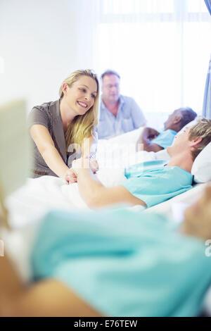 Woman talking to boyfriend in hospital room - Stock Photo
