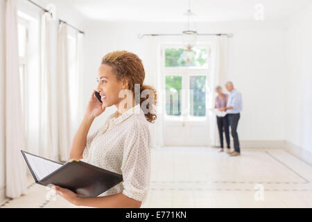 Woman talking on cell phone while couple looks at living room - Stock Photo