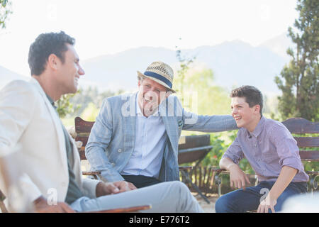 Three generations of men relaxing outdoors - Stock Photo