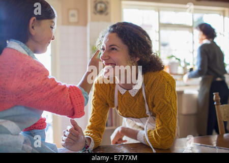 Mother and daughter playing in the kitchen - Stock Photo