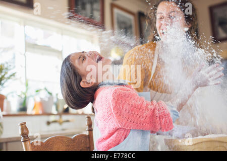 Mother and daughter playing with flour in the kitchen - Stock Photo