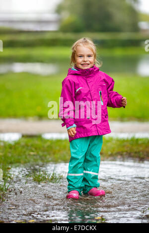 Happy little girl plays in a puddle - Stock Photo