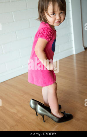 Baby girl in her mother's shoes - Stock Photo