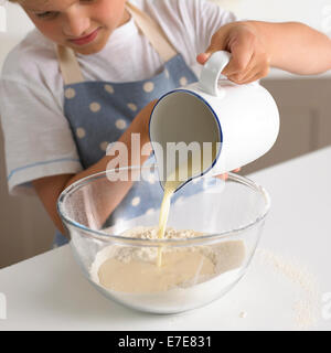 young boy 6-7 years pouring milk into flour to make batter for pancakes - Stock Photo