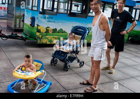 Fathers take car of his children in the streets of Shanghai. Shanghai has a lot to offer your kids when they get - Stock Photo