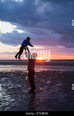 Father throwing his kid up in the air on the beach, silhouette shot - Stock Photo