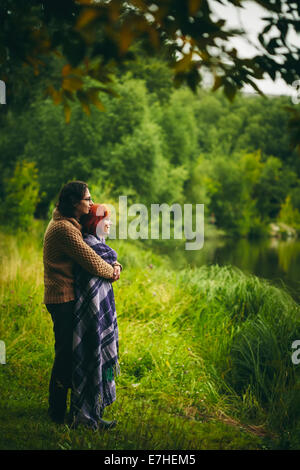 Young happy couple standing near water in green forest, looking ahead. Man holding woman. - Stock Photo