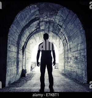 Young man stands in dark tunnel and looks in the glowing end - Stock Photo
