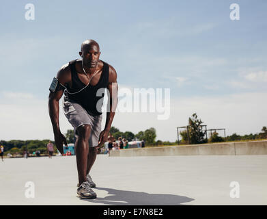 Fit young man on his mark to start running. Determined athlete outdoors. Muscular African male model ready for his - Stockfoto