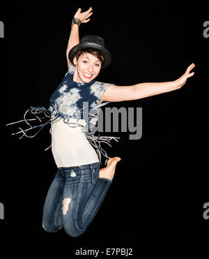 Portrait of young woman jumping - Stock Photo