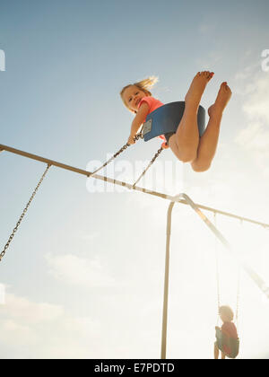USA, California, San Clemente, Girl (4-5) and boy (2-3) swinging on beach - Stock Photo