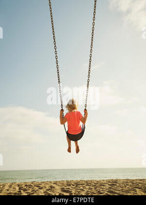 USA, California, San Clemente, Girl (4-5) swinging on beach - Stock Photo