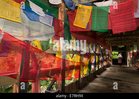 Eastern Bhutan, Trashi Yangtse, prayer flags lining old wooden bridge over Dongdi Chu river - Stock Photo