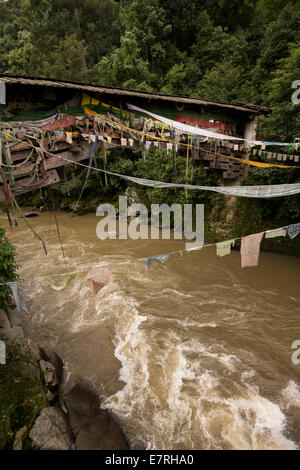 Eastern Bhutan, Trashi Yangtse, old wooden bridge over Dongdi Chu river decorated with prayer flags - Stock Photo