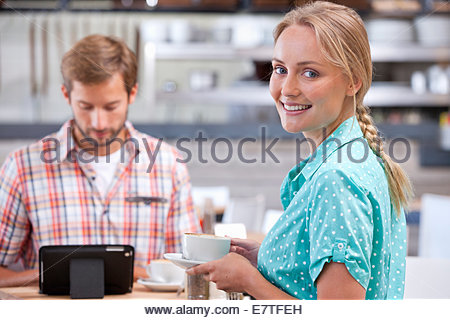 Smiling couple with digital tablet in coffee shop - Stock Photo