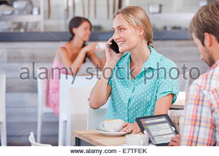 Smiling couple with digital tablet and cell phone in coffee shop - Stock Photo