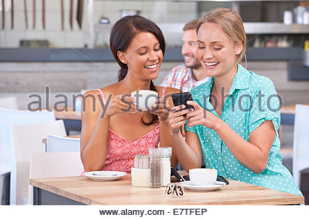 Smiling friends texting with cell phone in coffee shop - Stock Photo