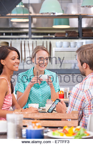 Friends using digital tablet in coffee shop - Stock Photo