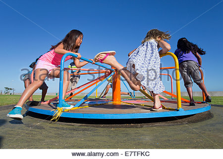 Children riding carousel in park - Stock Photo