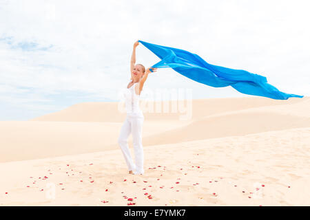Young slim woman wearing white with flying blue scarf in desert - Stock Photo