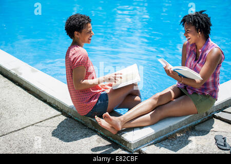 Two women sitting by the side of a swimming pool, reading books. - Stock Photo