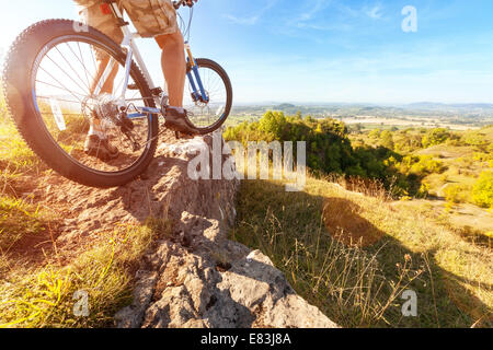 Mountain biker looking at downhill dirt track - Stock Photo