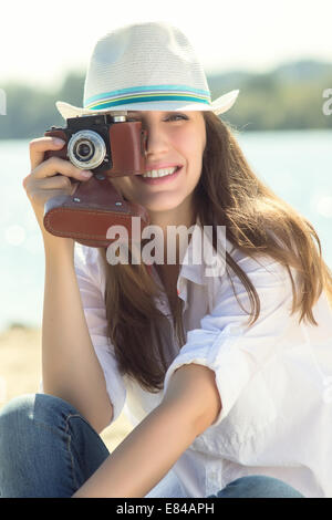 Smiling hipster woman with old camera at the beach. Young caucasian girl on vacation - Stock Photo