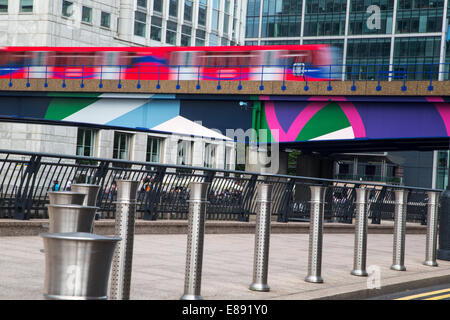 The Docklands light railway at Canary Wharf heading south - Stock Photo