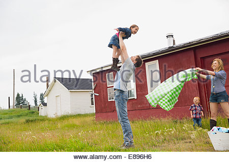Family playing in rural field - Stock Photo