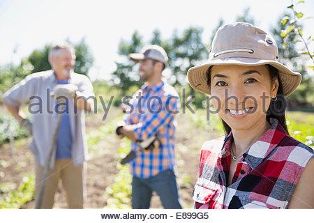 Portrait of smiling woman in community garden - Stock Photo