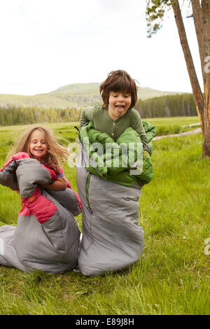 Boy and girl sack racing in sleeping bags - Stock Photo