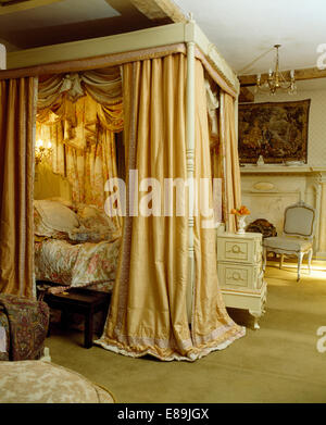 Opulent cream silk drapes on four poster bed in countgry bedroom - Stock Photo